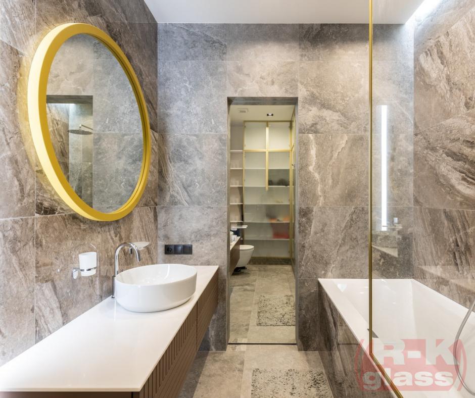 Okragłe lustro w złotej ramie zawieszone w łazience